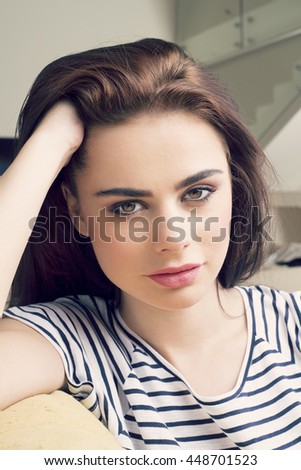 Pretty Young Woman Sitting on Couch In the Living Room , Beautiful young girl relaxing at home  - stock photo