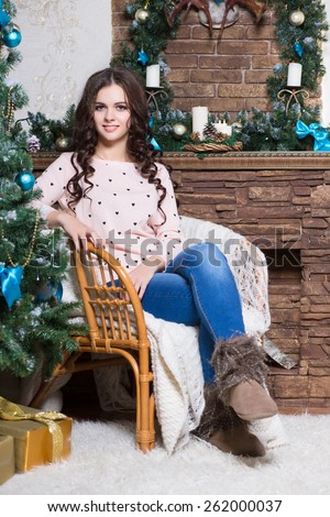 Pretty young woman sitting on the chair near fir-tree and fireplace - stock photo