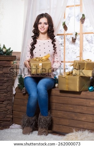 Pretty young woman sitting on the windowsill holding a golden gift box - stock photo