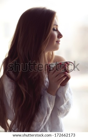 pretty young woman sitting  with a cup of tea - stock photo