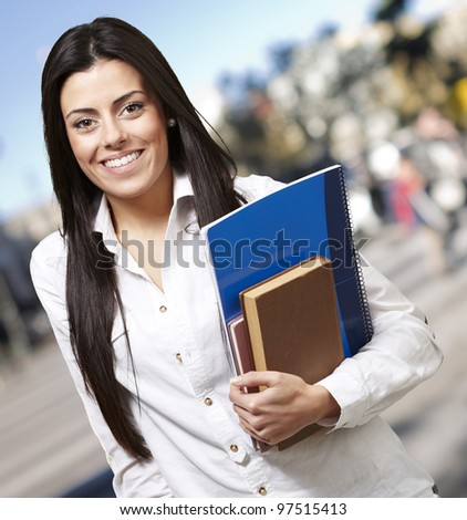 pretty young woman smiling and holding notebooks against a street background - stock photo