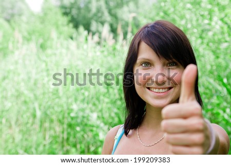 pretty young woman smiling and showing thumbs up - stock photo
