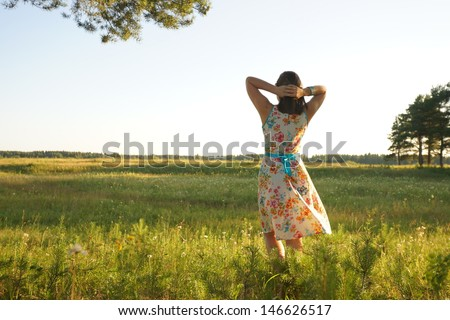 Pretty young woman stand in grass field - stock photo