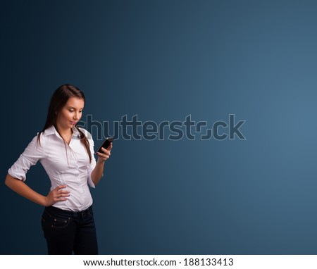 Pretty young woman standing and typing on her phone with copy space - stock photo