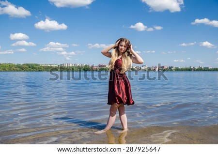 Pretty young woman standing on a beach and enjoying the sun - stock photo