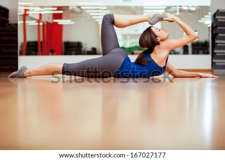 Pretty young woman stretching and getting ready for her yoga class - stock photo