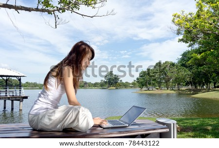 Pretty young woman surfing internet on laptop outdoors. - stock photo