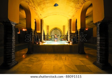 Pretty young woman taking a bath in the Arab baths in Granada, Andalucia, Spain - stock photo