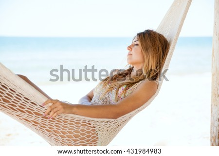 Pretty young woman taking a nap in a hammock during her vacation at the beach - stock photo