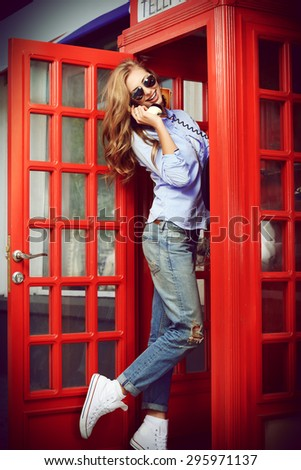 Pretty young woman talking on the phone in telephone booth. Europe, England. Vacation, tourist trip. - stock photo