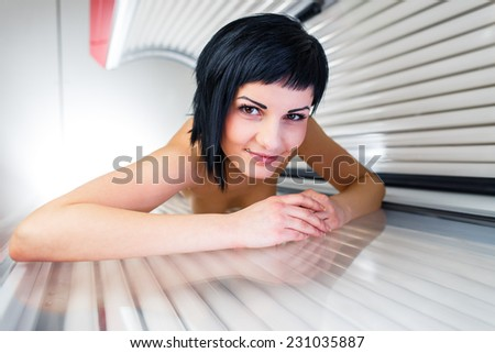 Pretty, young woman tanning her skin in a modern solarium/sunbed - stock photo