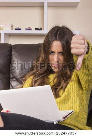 Pretty young woman using gadget while relaxing on sofa at home - stock photo