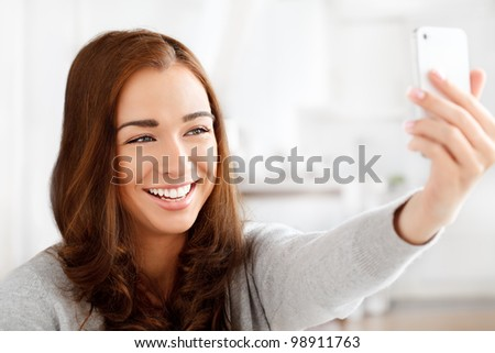 Pretty young woman using mobile phone - stock photo