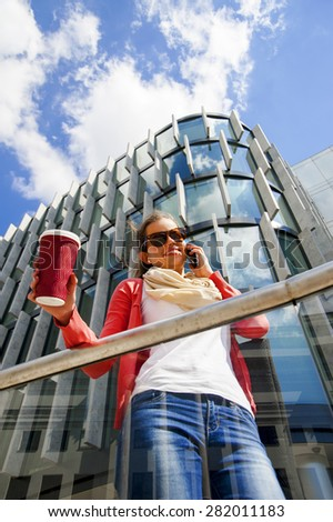 Pretty young woman using mobile phone holding coffee cup - stock photo