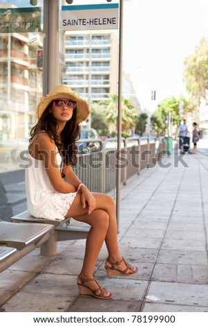 Pretty young woman waiting for a bus in the French Riviera in Nice, France. - stock photo