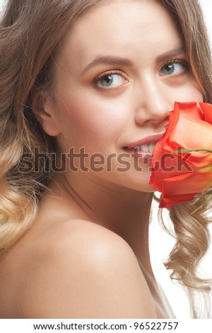 Pretty young woman with beautiful make-up and perfect healthy skin sniffing rose - stock photo