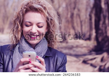 Pretty young woman with blond curly hair typing on the phone in outdoors.She is smiling as she is communicating with her friends via social networks. - stock photo