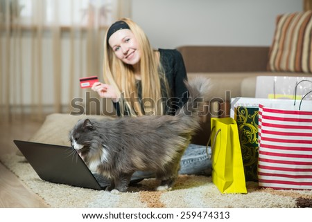 Pretty young woman with her cat making online shopping at home.  - stock photo