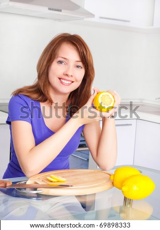 pretty young woman with lemons in the kitchen at home - stock photo