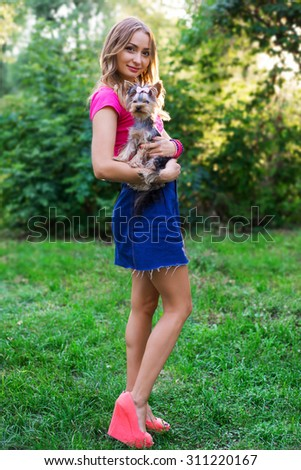 pretty young woman with little dog on her hands outdoor.  - stock photo