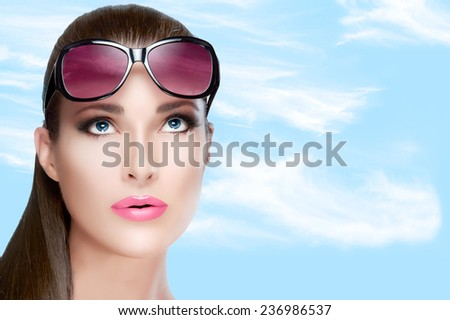 Pretty Young Woman with Long Straight Hair Wearing Stylish Red Violet Shades on Forehead, Looking up. Closeup portrait over blue sky with white clouds . Bright makeup. Beauty and Fashion Concept - stock photo