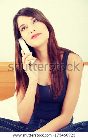 Pretty young woman with phone sitting on bed at home  - stock photo