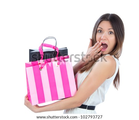 Pretty young woman with shopping bags after successful shopping, smiling and looking at the camera on a white background - stock photo