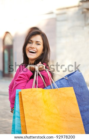 Pretty young woman with shopping bags in the city. Shopping concept - stock photo