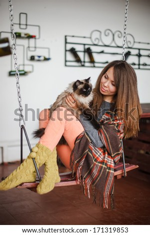 Pretty young woman with siamese cat in  warm wool socks with plaid sitting on a swing at home  - stock photo