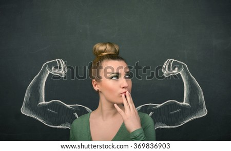 Pretty young woman with sketched strong and muscled arms - stock photo