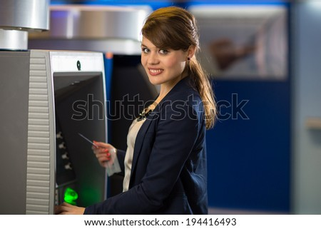 Pretty, young woman withdrawing money from her credit card in at an ATM (shallow DOF; color toned image) - stock photo