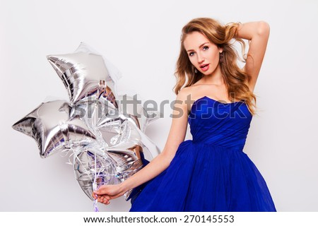 Pretty young women celebrate  birthday  and holding  silver party balloons. Wearing blue evening stylish  dress and have day of against white wall. - stock photo