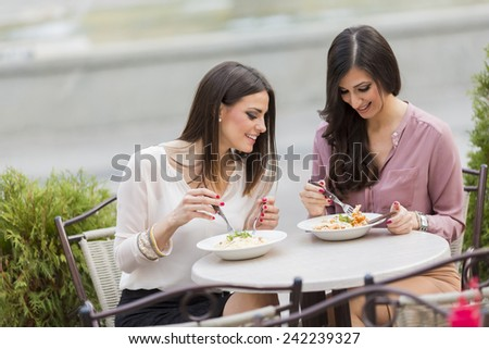 Pretty young women having lunch in the restaurant - stock photo