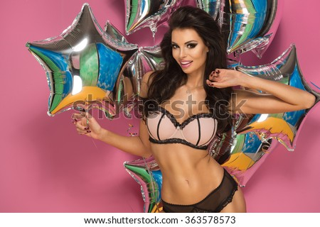 Pretty young women holding silver party balloons. Wearing lingerie.  - stock photo