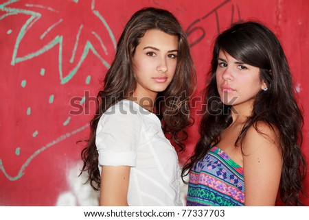 Pretty young women in a outdoor fashion scene with a red graffiti background. - stock photo