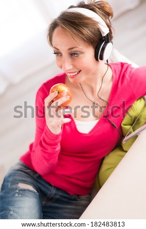 pretty young women on a sofa, listening music on her tablet computer and eating an apple - stock photo