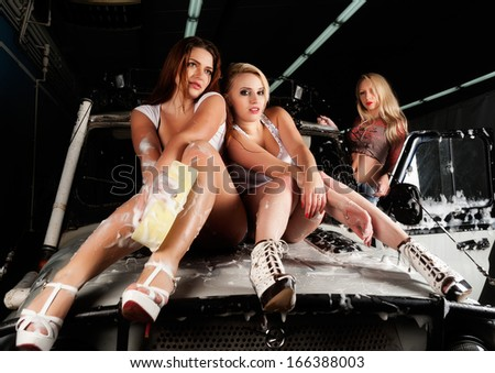 Pretty young women washing offroad car by sponge - stock photo