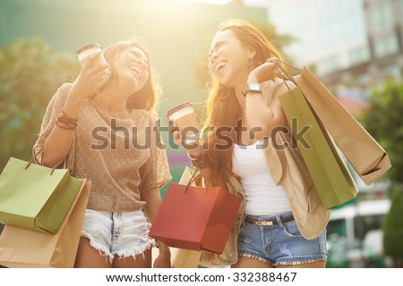 Pretty young women with shopping bags having fun together - stock photo