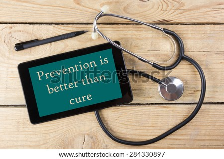 Prevention is better than cure  - Workplace of a doctor. Tablet, medical stethoscope, black pen on wooden desk background. Top view - stock photo