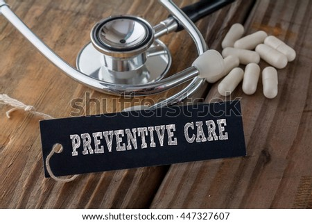 Preventive Care written on label tag with pills and Stethoscope on wood background - stock photo