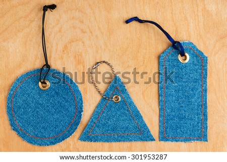 Price tags made of jeans, lying on the wooden background - stock photo