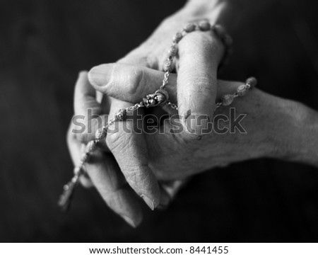 Priest hand holding rosary over black, dramatic look isolated on black - stock photo