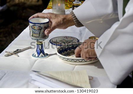 Priest hands during open air mass - stock photo