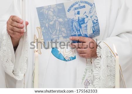 Priest holding baptism book - stock photo