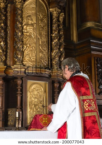 Priest opening the 17th century tabernacle in a medieval church with baroque interior - stock photo