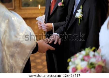 priest putting ring on groom's finger - stock photo