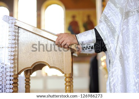 priest's hand on chancel at church - stock photo