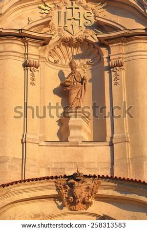 Priest sculpture decorates the Baroque facade of Saint Nicholas Church (Cathedral), Prague, Czech Republic - stock photo