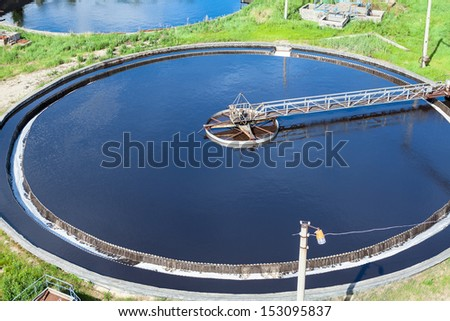 Primary round sedimentation basin, sewage flowing through large tanks - stock photo