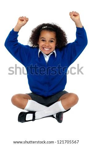 Primary school girl grinding her teeth in excitement. Sitting on floor with crossed legs. - stock photo